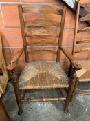 Oak framed ladder back open arm chair with string seat