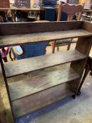 Open bookcase with four graduated shelves, and two carved implements