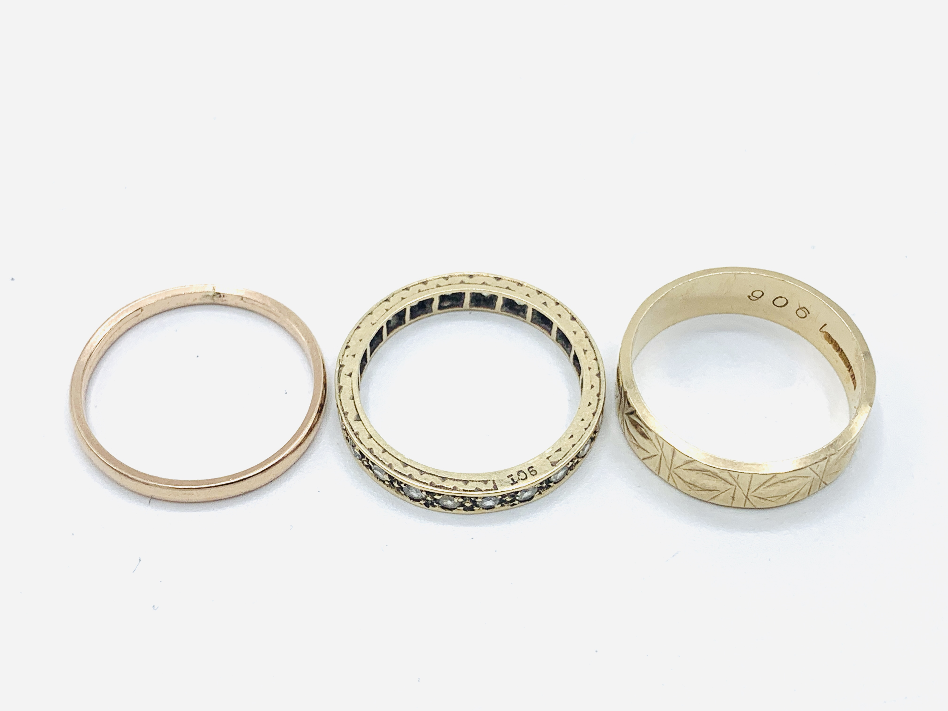 A 9ct gold band, a 9ct gold decorated band; and a 9ct gold and white stone eternity ring - Image 2 of 3
