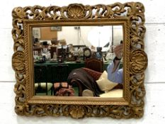 Ornately decorated gilt framed wall mirror