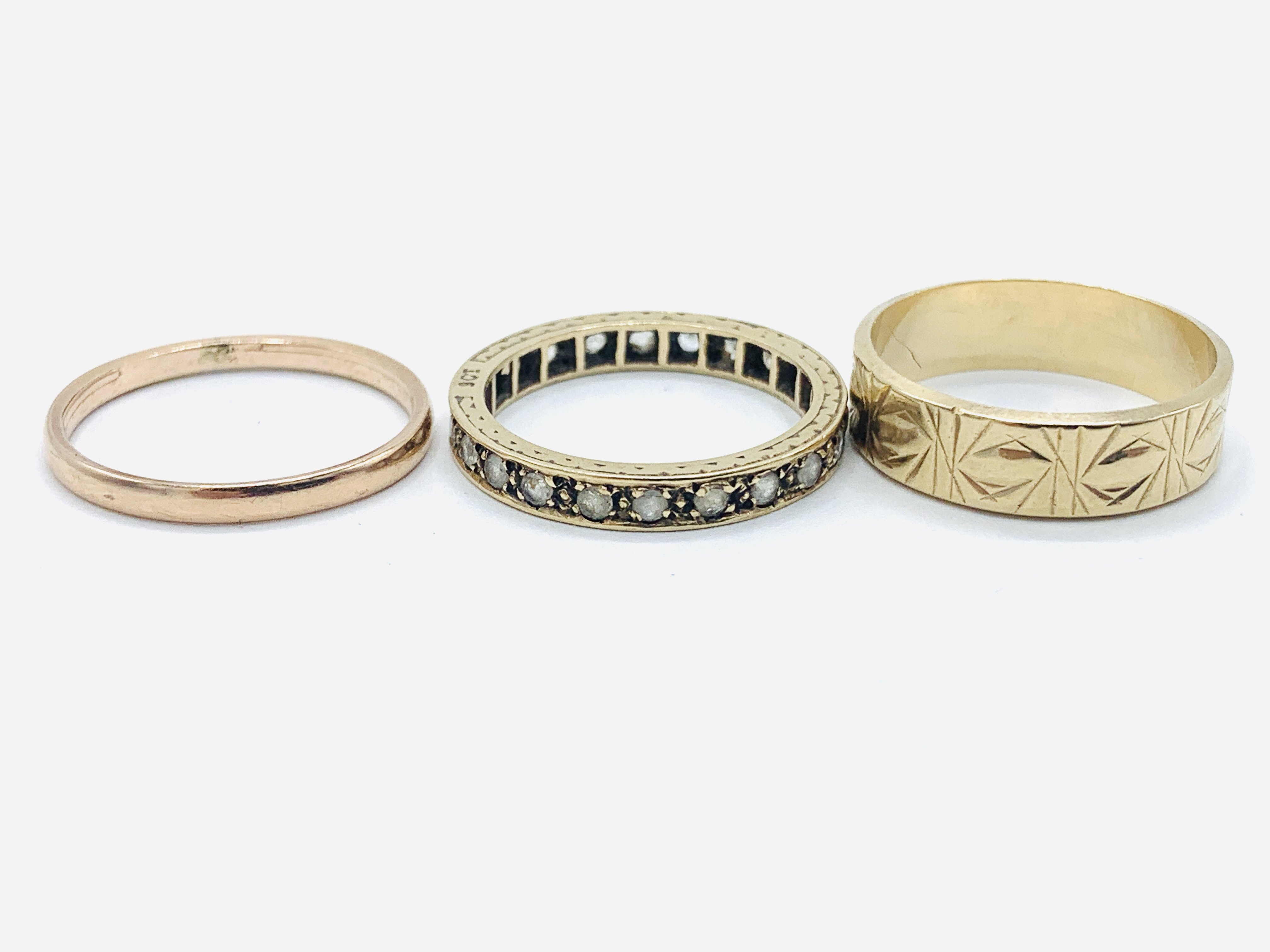 A 9ct gold band, a 9ct gold decorated band; and a 9ct gold and white stone eternity ring - Image 3 of 3