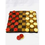 Inlaid chequerboard together with 14 red and 13 white draughts