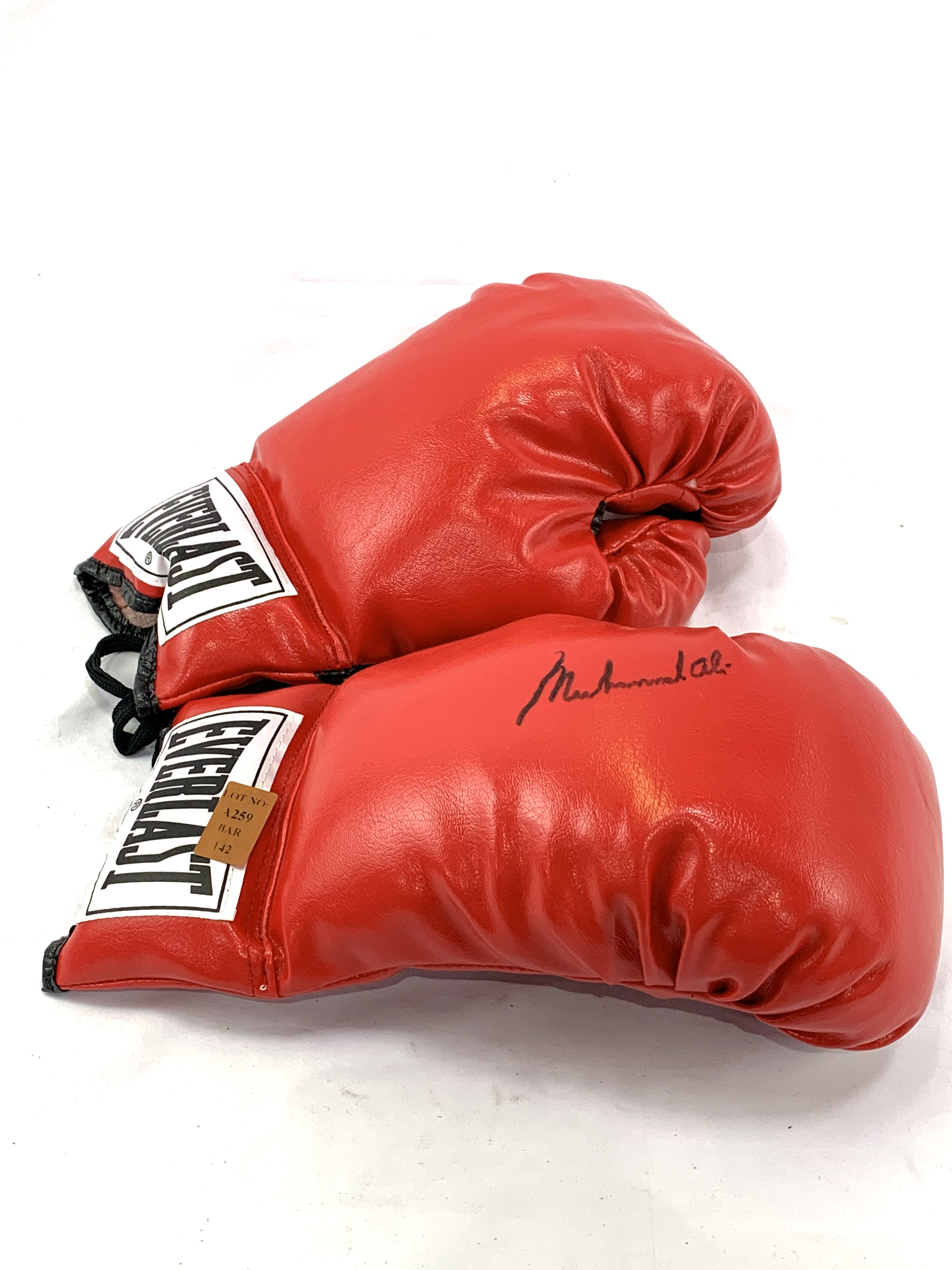Pair of red Everlast boxing gloves, one signed Muhammad Ali
