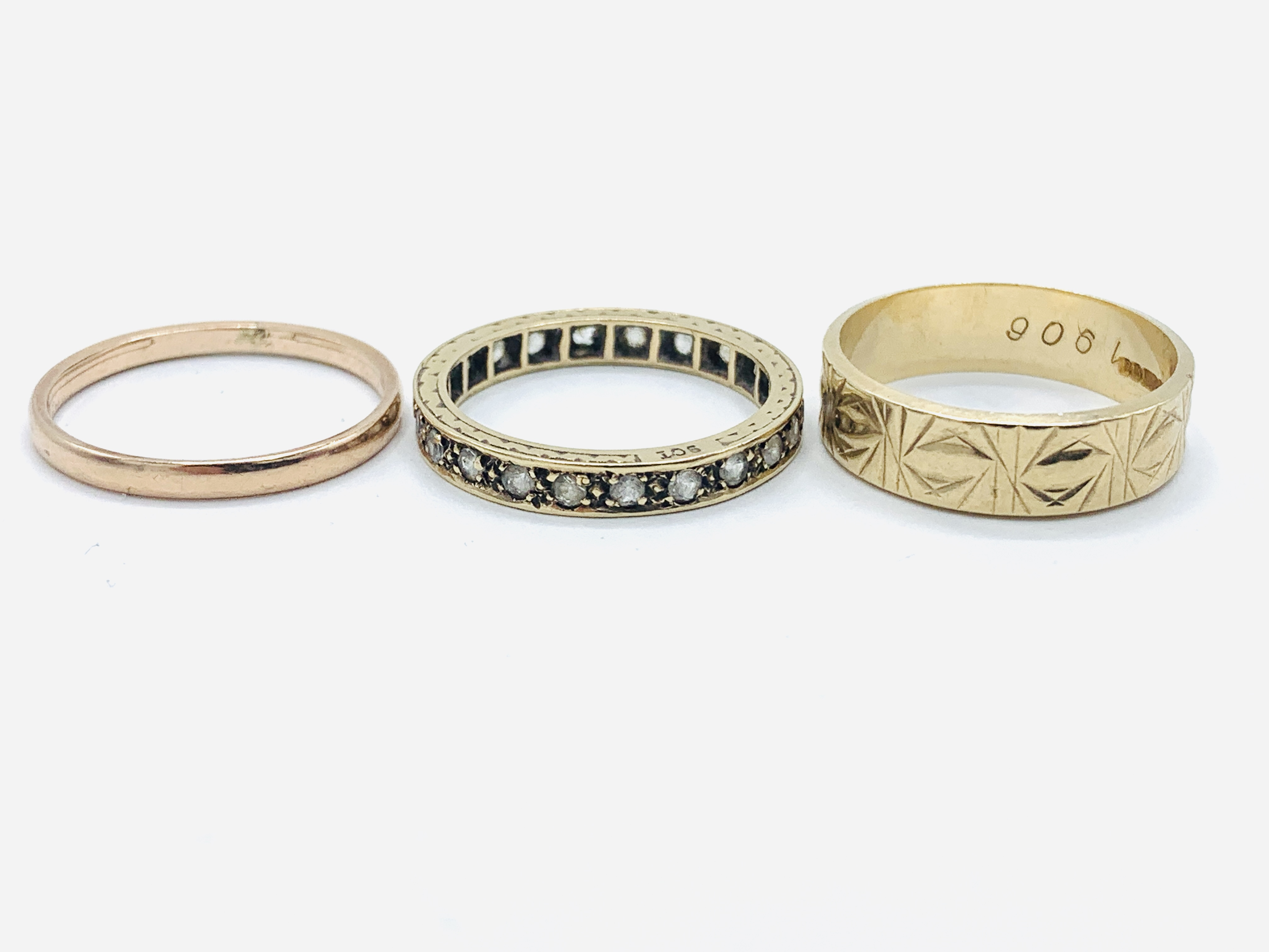 A 9ct gold band, a 9ct gold decorated band; and a 9ct gold and white stone eternity ring