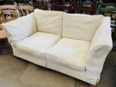 Cream upholstered two seat sofa