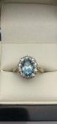 18 carat yellow gold ringSet with blue oval topaz surrounded by diamondsSize L