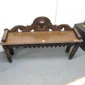 An antique oak bench, carved mask back and bobbin