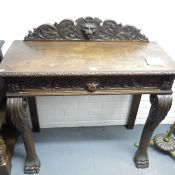 A carved oak serving table, carved mask and scroll