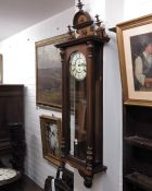 A Vienna mahogany cased wall clock, mask carved pe