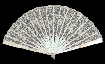 A first quarter 19th century Carrickmacross needle lace fan, the crisp leaf mounted on pink Mother o