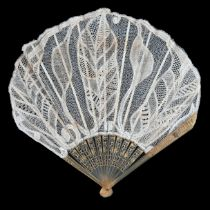 Circa 1900 to 1915, an unusual lace fan in fontange form, the monture of carved, pierced and lightly