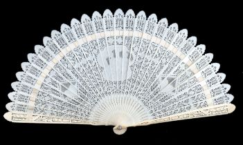 An early 19th century carved and pierced ivory brisé fan with 22 slender sticks, and two guards, the
