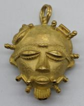 An 18ct gold African mask pendant/brooch, marks for 18ct and tested as 18ct, 35g, L.4cm