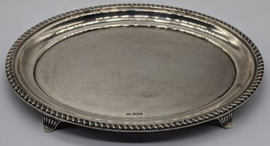 An early 20th century silver oval stand, raised on four splay feet, hallmarked Sheffield 1931, maker