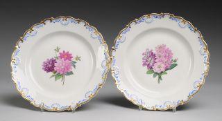 Paar Berliner Teller mit BlumenmalereiWeiß, glasiert. Gemuldete Form mit geknickt-geschweift