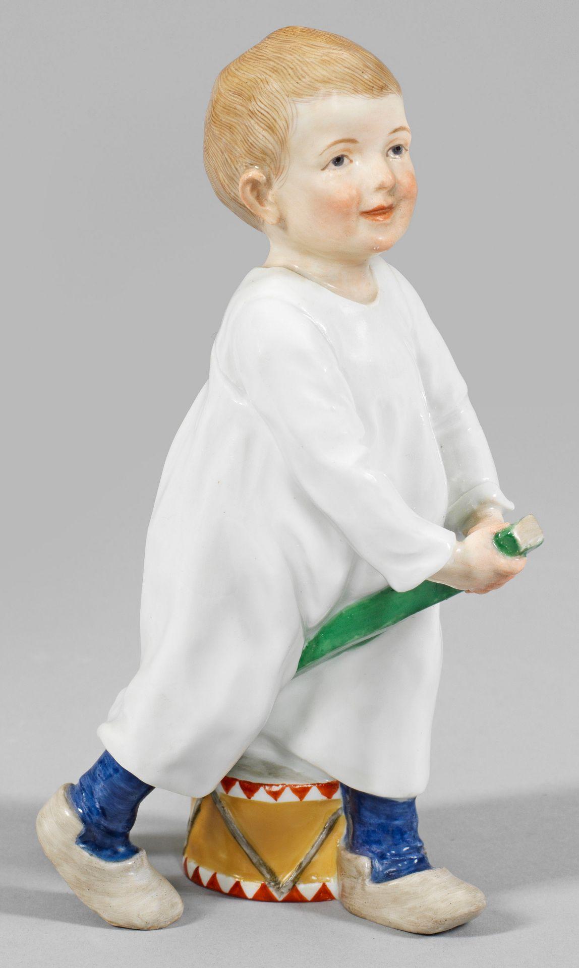 Auf einem Stecken reitendes Kind mit Trommel