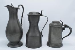 Early 19th century pewter to include a flagon, a jug and a lidded tankard (3) As expected. Flagon