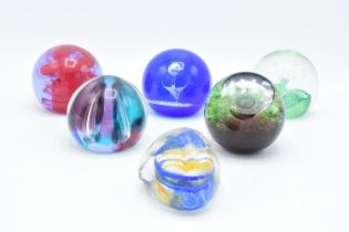 A collection of Caithness glass paperweights to include Pebble, Scimitar, Nebula, Moonlight