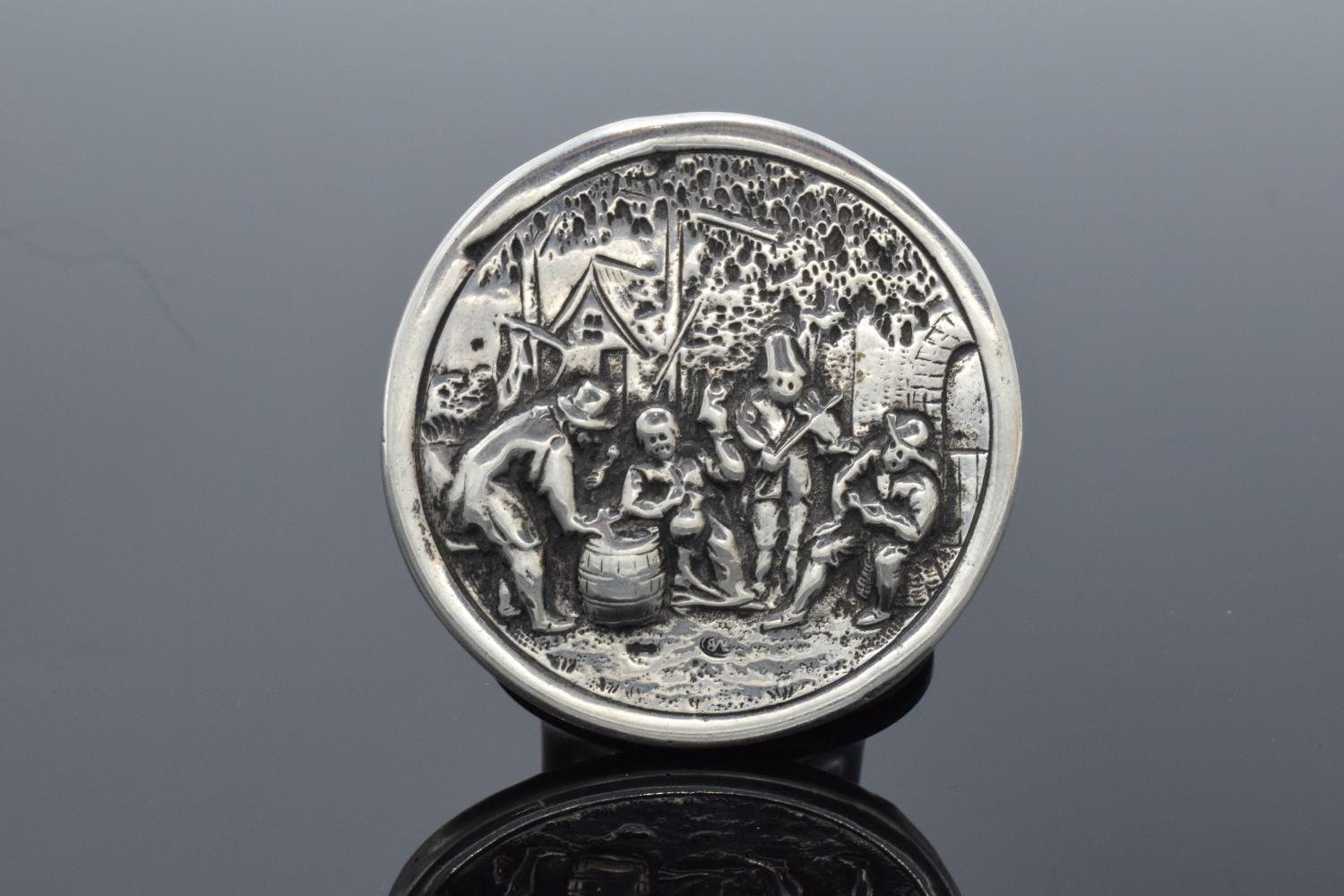 A late 19th/ early 20th century circular silver brooch depicting dutch style scenes with a base