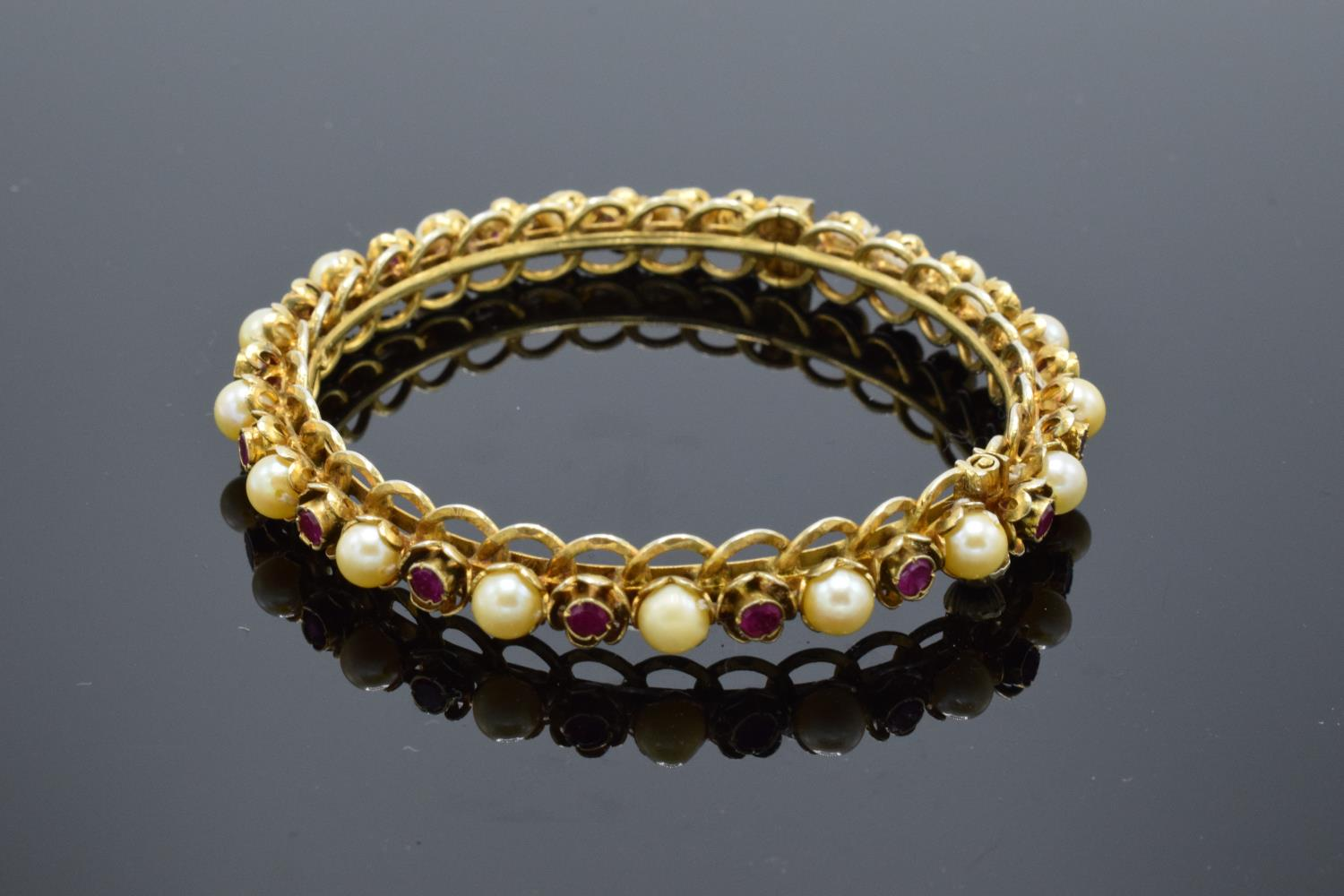 Quality silver gilt bangle set with ruby and pearl stones.