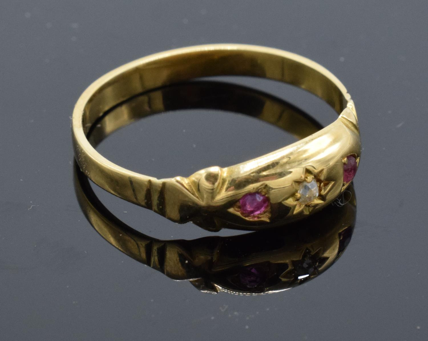 18ct gold ladies ring set with rubies and a diamond stone. UK size P/Q. Gross weight 2.2 grams.