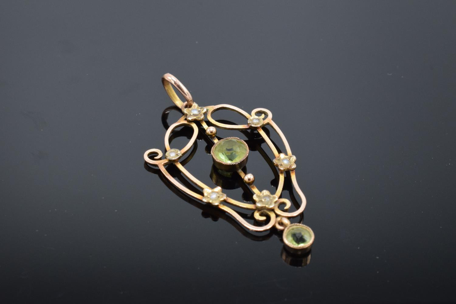 An antique 9ct gold ornate pendant set with peridot and pearls. Gross weight 2.1 grams. Stamp to