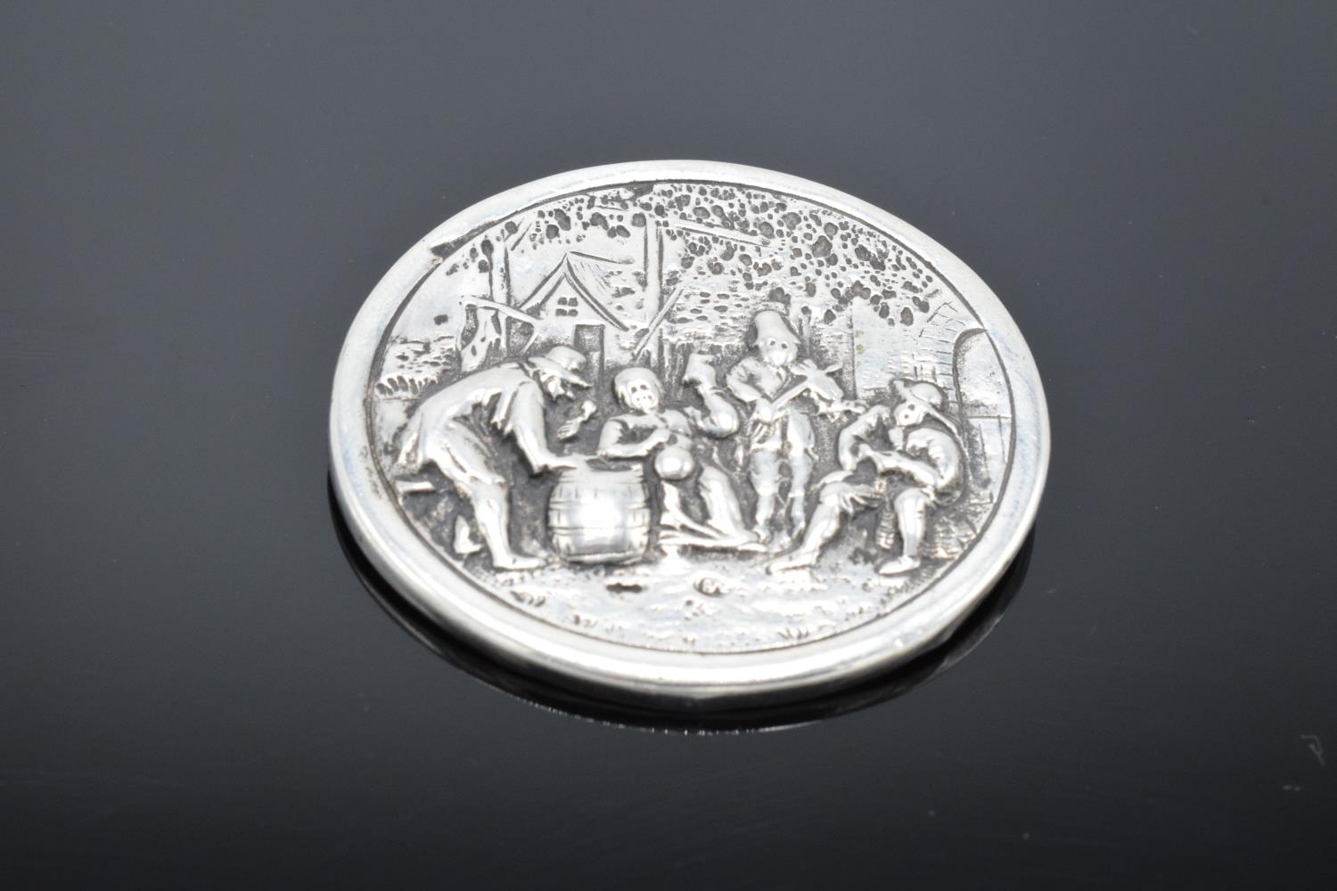 A late 19th/ early 20th century circular silver brooch depicting dutch style scenes with a base - Image 4 of 4