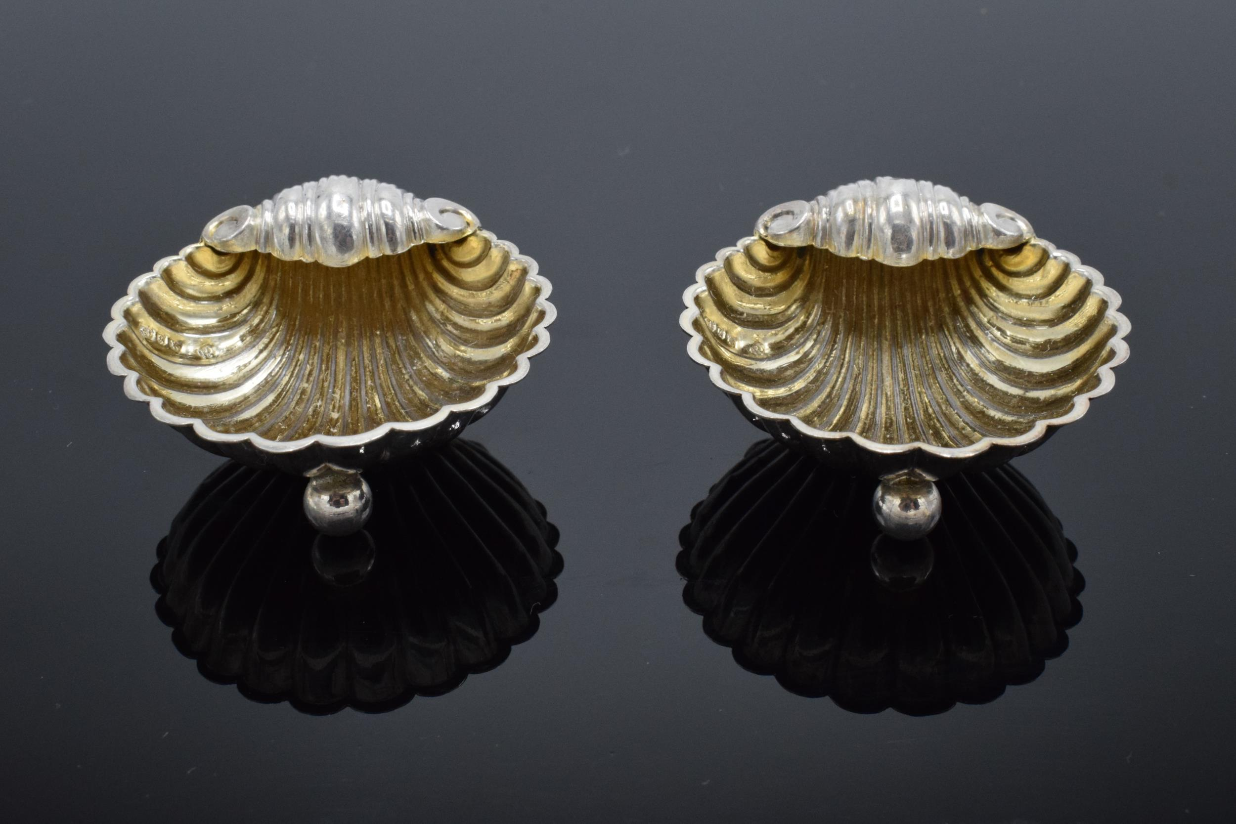 A pair of silver table salts in the form of shells raised on ball feet. Hallmarked for Birmingham