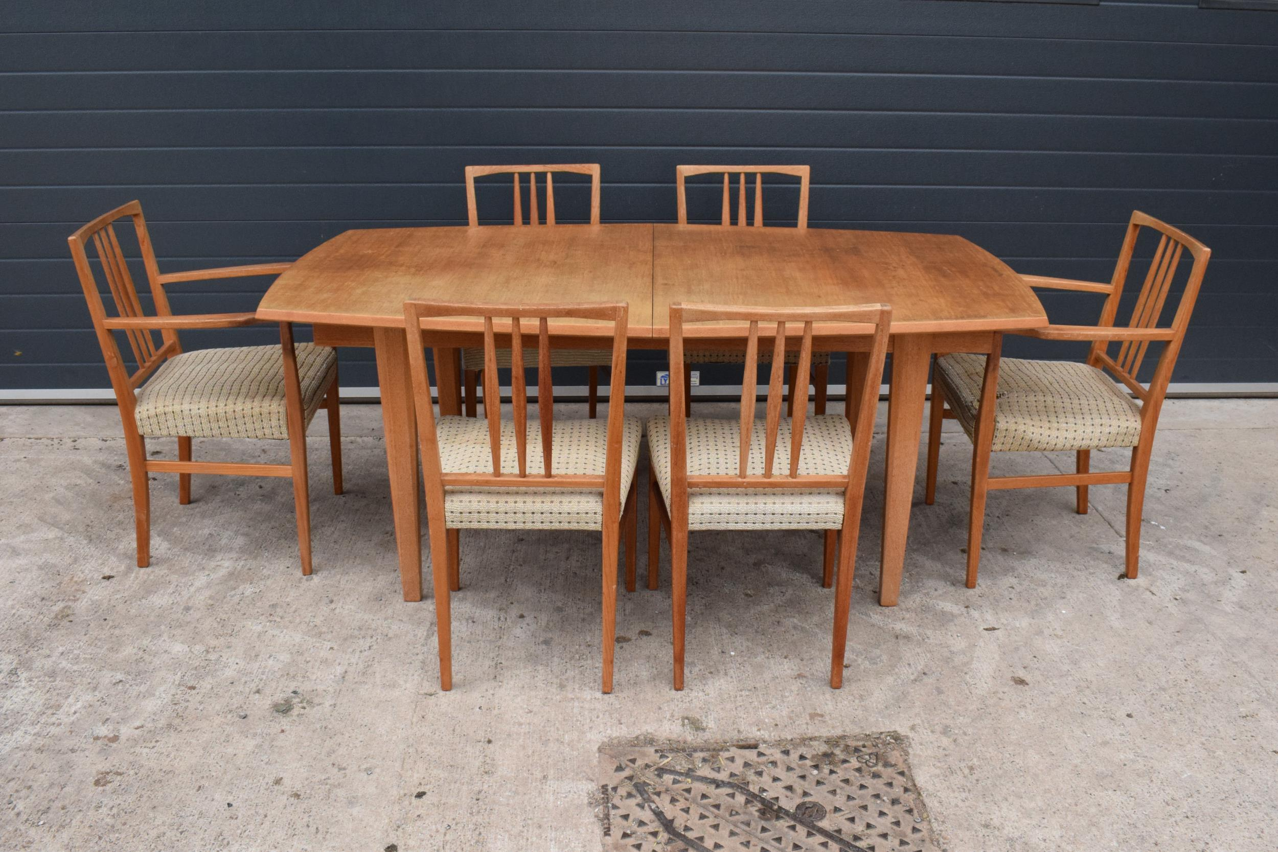 A mid century / retro Gordon Russell extending shaped rectangular dining table together with 6
