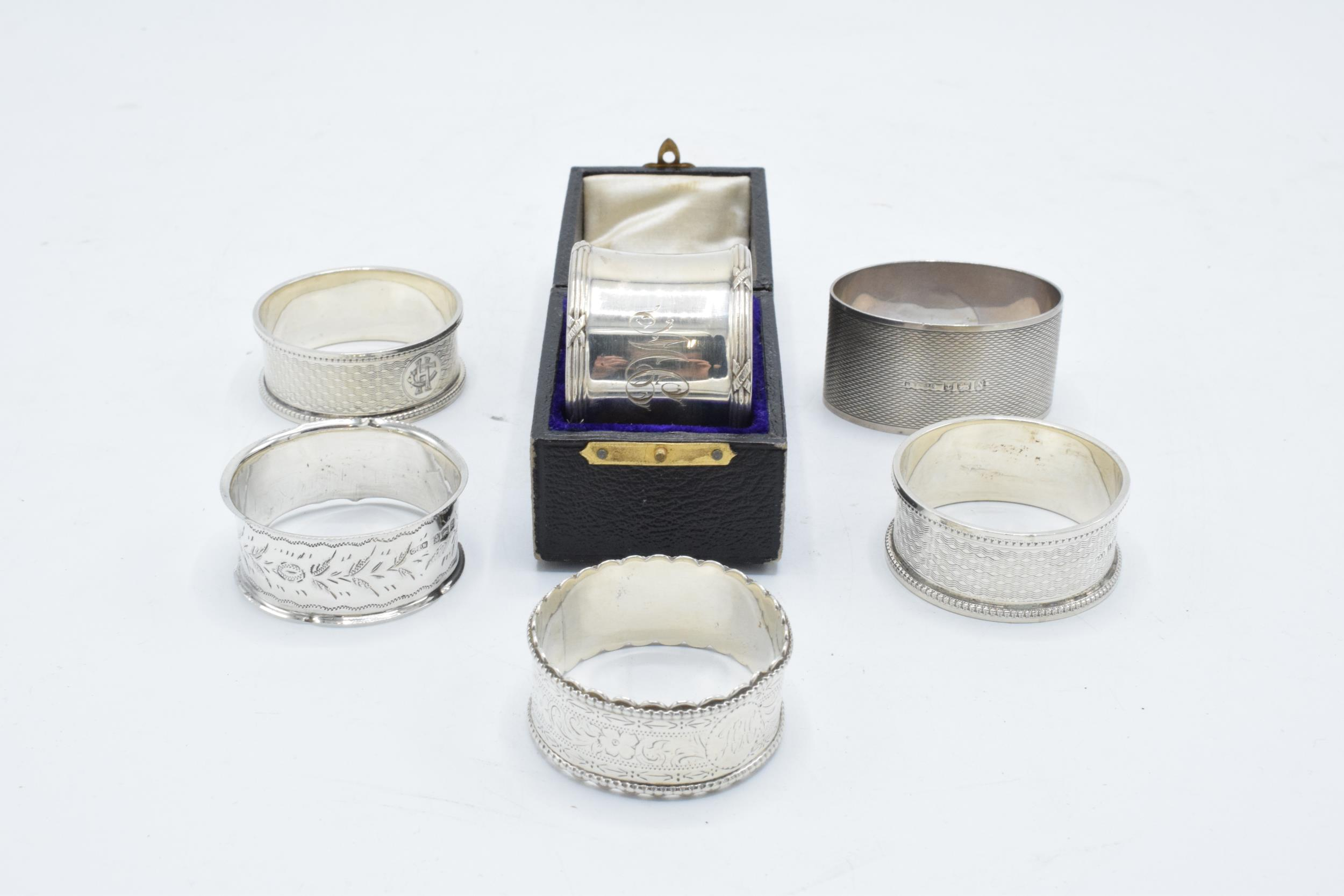 Group of 6 silver napkin rings. All hallmarked, 4 rings with engraved initials, 1 has a case. weight