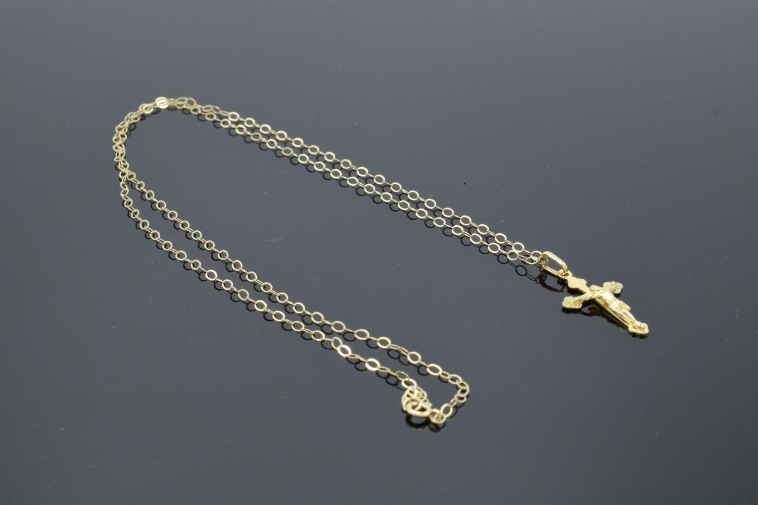 A 9ct gold (stamped 375 Italy) crucifix pendant on a gold chain. 0.8 grams. 46cm in length with