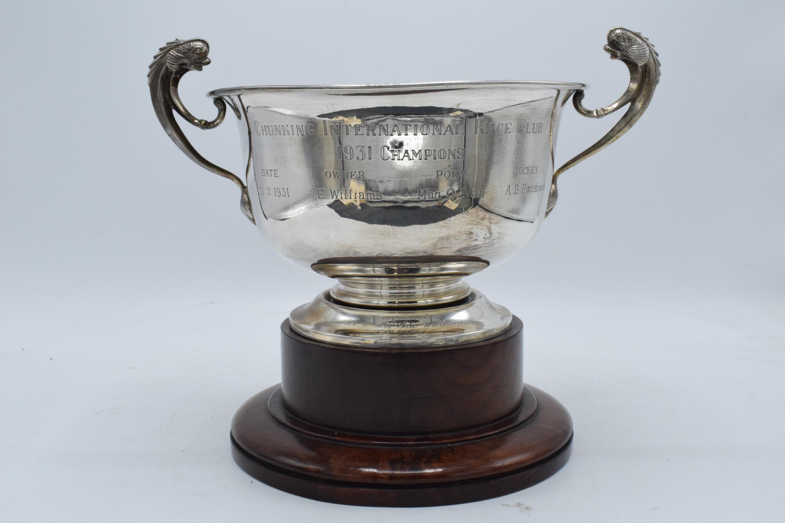 A large silver pedestal bowl raised on a turned wooden plinth with ornate handles. Circa 700