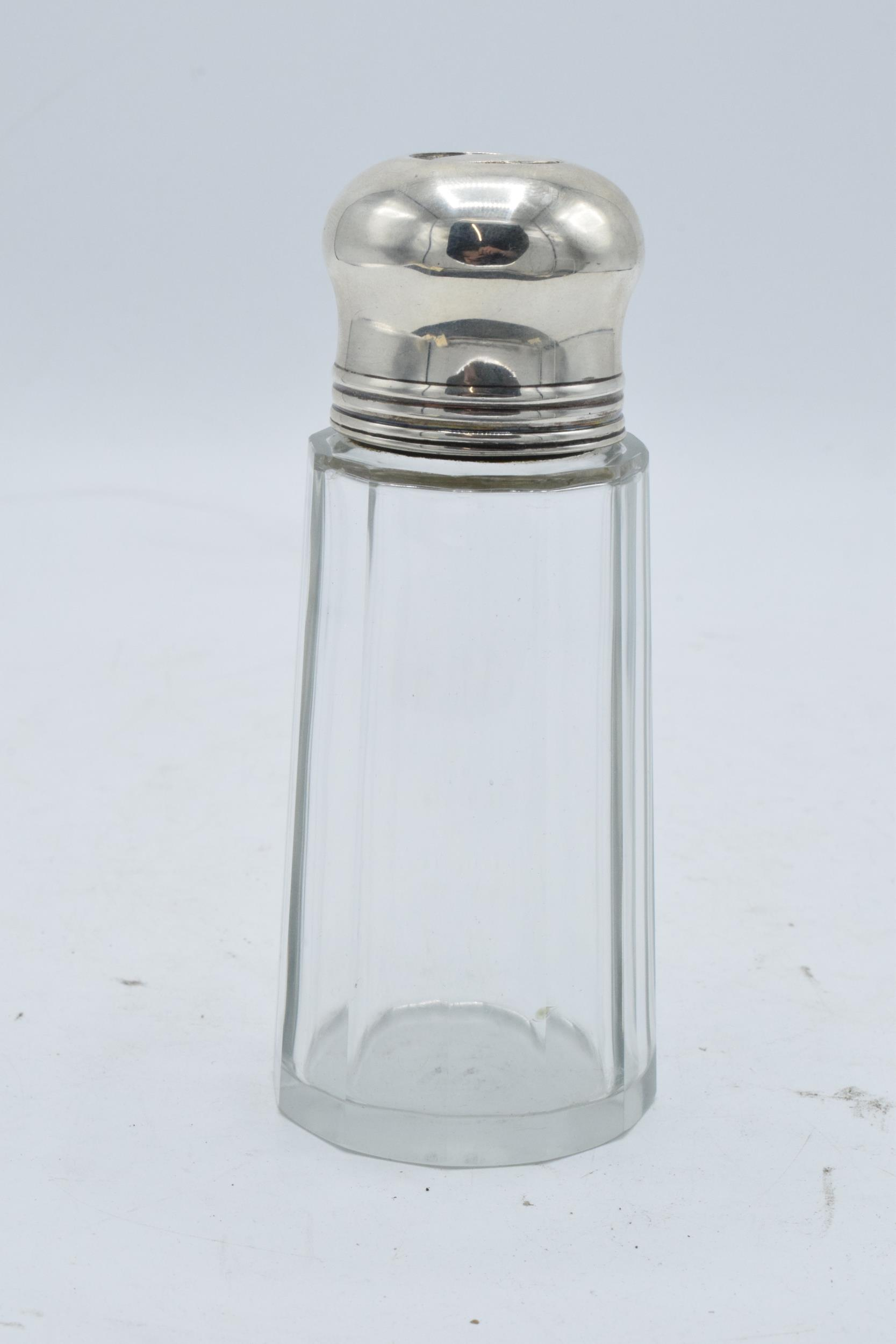A glass and silver topped sugar sifter. Birmingham 1923. In good condition.