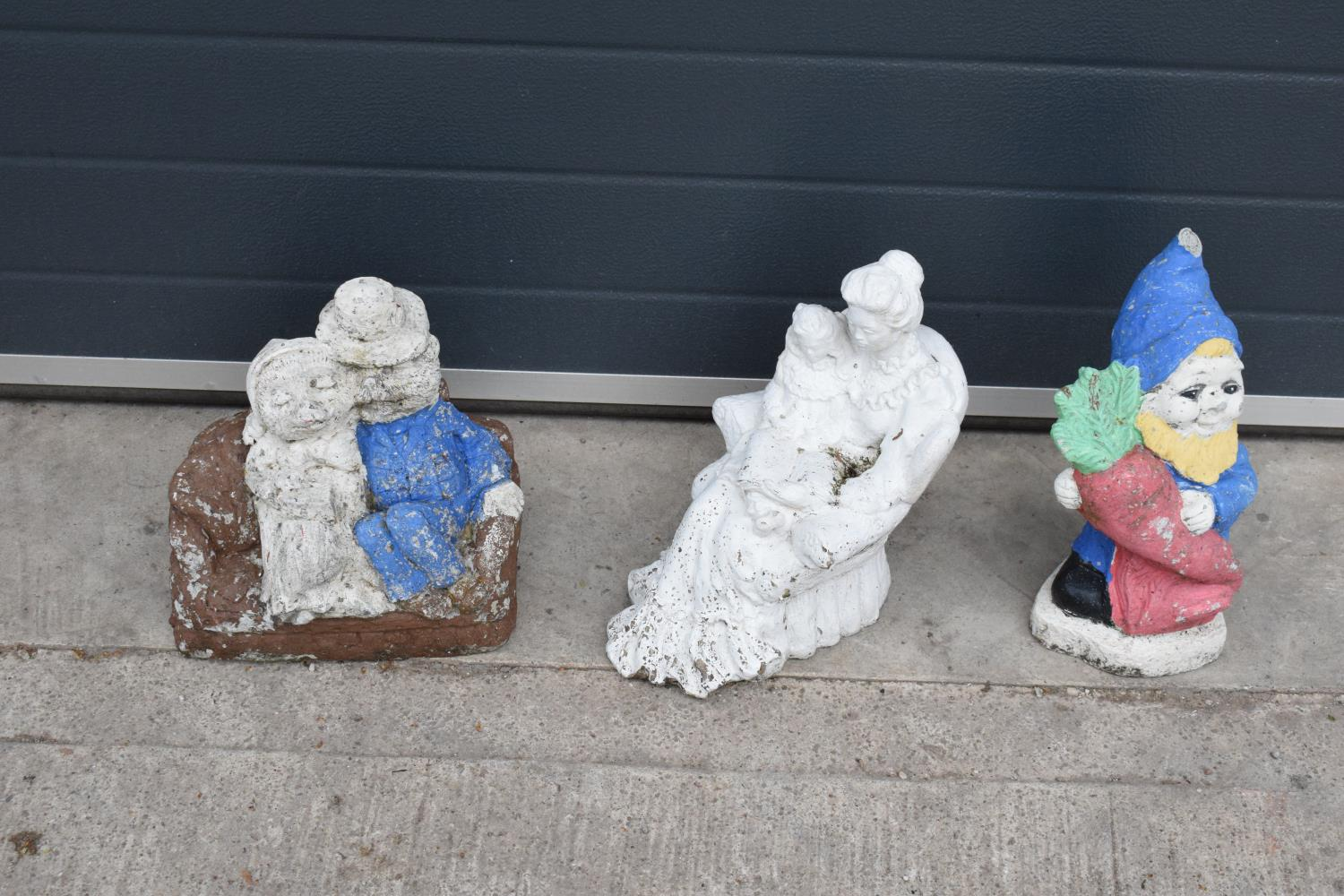 A collection of vintage garden ornaments to include a garden gnome, a figure of a couple and one