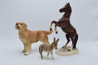 A collection of pottery to include a Beswick donkey foal 2110, a Hertwig rearing horse and an