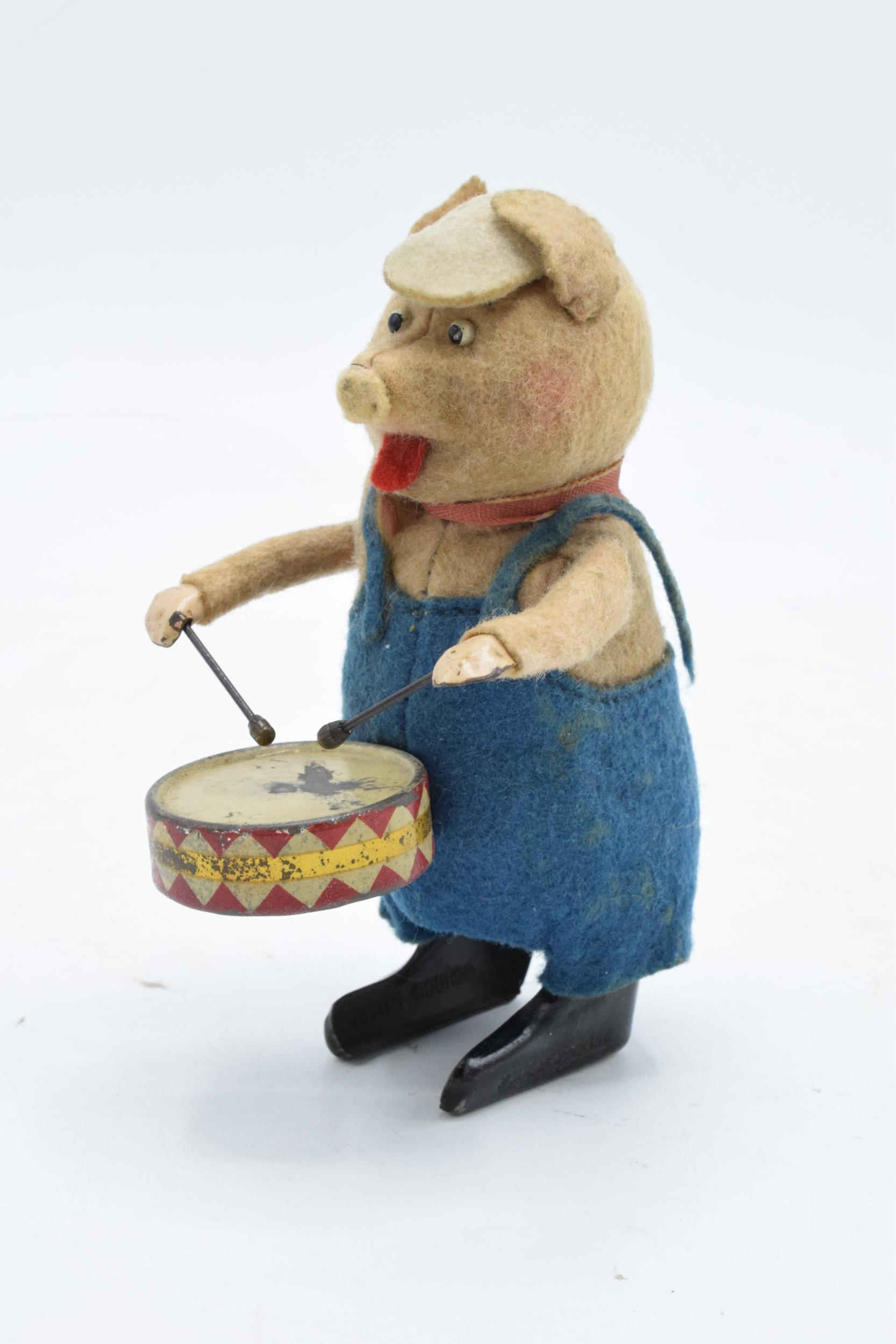A Schuco circa 1930s clockwork toy figure in the form of a pig with a drum. Based on the Three