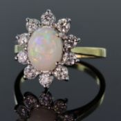 Tests as 18ct yellow gold cluster ring set with a central oval shaped opal cabochon measuring