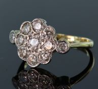 18ct yellow gold diamond cluster ring consisting of a central round brilliant cut diamond calculated