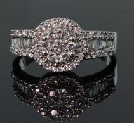 14ct white gold diamond cluster ring consisting of a central raised cluster of seven round brilliant