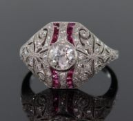 Platinum diamond and ruby Art Deco style bombe shaped ring set with a central round brilliant cut