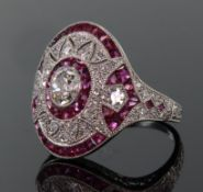 Platinum ruby and diamond ring comprising a central oval diamond weighing 0.49ct surrounded by a row