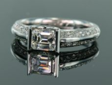 18ct white gold diamond ring consisting of central emerald cut bar set diamond weighing 0.79ct, with