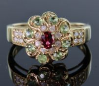 9ct yellow gold cluster ring consisting of central oval 4mm x 3mm ruby, surrounded by eight round