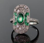 Platinum emerald and diamond Art Deco style elongated oval ring comprising central oval emerald
