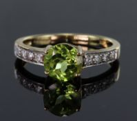 9ct yellow gold ring set with round 7mm peridot weighing 1.168ct in a four claw setting, bordered