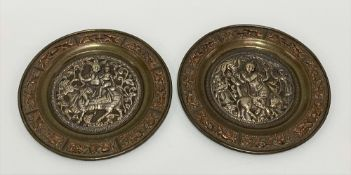 A pair of Indian brass, copper and white metal applied embossed circular dishes, the wells both