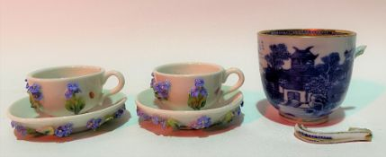 Pair of miniature German porcelain forget-me-not encrusted tea cups and saucers painted with