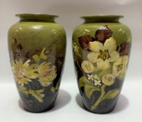 A pair of Burmantofts faience floral decorated vases upon a green and brown blush ground, both