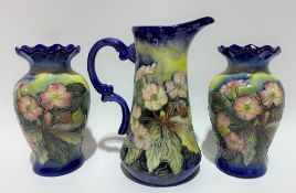 Old Tupton ware jug with pair of matching baluster vases, foliate decorated upon a dark blue ground,