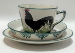 A Wemyss ware black cockerel decorated trio impressed and printed marks and retailed for T.